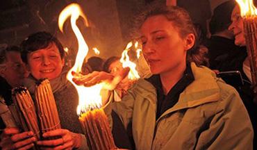 I pellegrini che sperimentano incuriositi il misterioso fenomeno della fiamma che non brucia