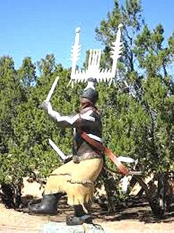 """La raffigurazione di Ga'an, il dio celeste degli Apache, elargitore della """"danza sacra"""". Sul suo capo è evidente il """"siv'nul"""", il candeliere dalle tre braccia, simbolo della tradizione di Fetonte"""