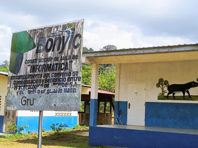 "In the Naso community of Solón, a peeling, faded plaque from the company behind the Bonyic plant stands in front of an ""IT classroom"" seemingly bearing no computers"